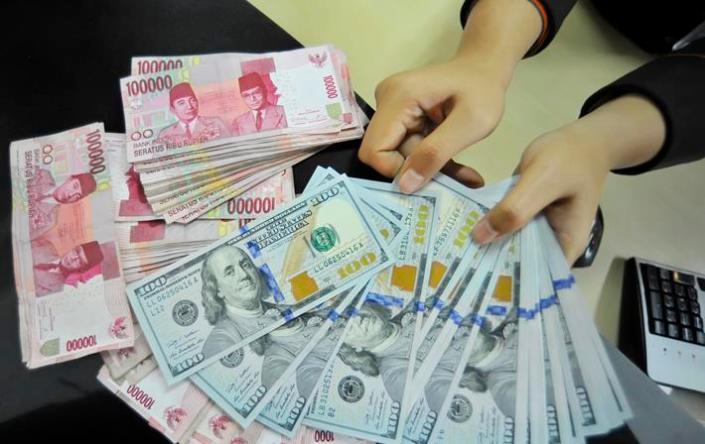 Petugas menghitung uang pecahan Dolar AS di layanan nasabah Bank BNI, Jakarta, Senin (26/1). Mata uang Rupiah melorot ke level Rp 12.515 per dollar AS, selain euforia rencana pembelian obligasi oleh Bank Sentral Uni Eropa (ECB), pelemahan Rupiah dipicu 'flight to quality' sehingga penguatan dollar AS akan memicu pelemahan mata uang global terhadap dollar termasuk rupiah. ANTARA FOTO/Yudhi Mahatma/pd/15